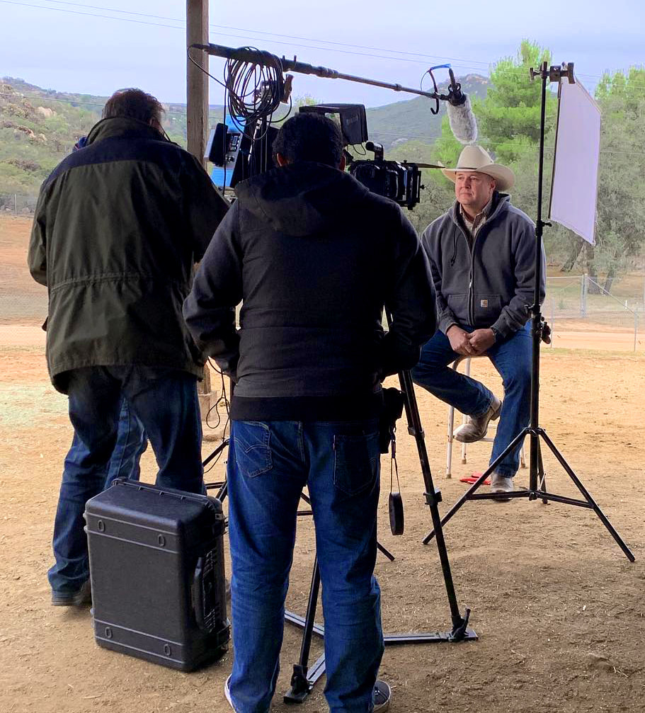 Behind the scenes picture interviewing a cowboy.